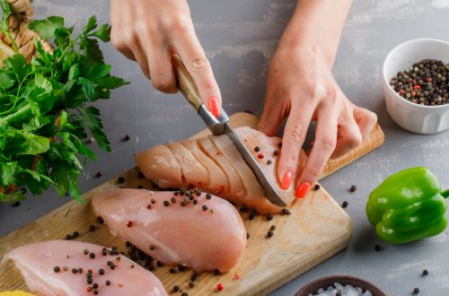 Woman cutting raw chicken